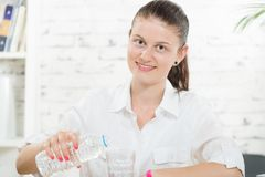 Pretty young woman pours glass of water Stock Photography