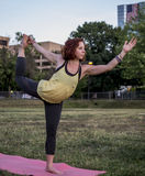 Pretty Young Woman Practicing Yoga in the Park (Dancer Pose) Royalty Free Stock Photography