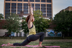 Pretty Young Woman Practicing Yoga in the Park (Low Lunge) Royalty Free Stock Image