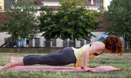 Pretty Young Woman Practicing Yoga in the Park (Low Plank) Royalty Free Stock Images