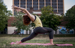 Pretty Young Woman Practicing Yoga in the Park (Warrior) Royalty Free Stock Photos