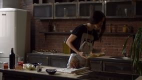 Pretty young woman putting baking pan into oven stock footage