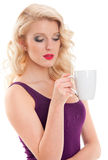 Pretty young woman in purple T-shirt is holding cup of coffee Stock Photos