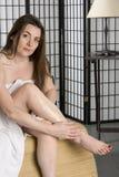 Pretty young woman puting on moisturizing lotion Stock Photography