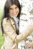 Pretty young woman puts her arms around a tree. Smiling pretty young woman holds her arms around a tree royalty free stock images