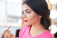 Pretty young woman putting on red lipstick Royalty Free Stock Images