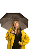 Pretty young woman in a raincoat with umbrella. A pretty young woman in a raincoat and holding an umbrella checks to see if it is raining (isolated against white stock photo