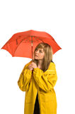 Pretty young woman in raincoat with umbrella. A pretty young woman, isolated against a white background, wears a bright yellow raincoat and holds an umbrella stock photos