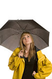 Pretty young woman in raincoat with umbrella. A pretty young woman, isolated against a white background, wears a yellow raincoat and holds a black umbrella stock images