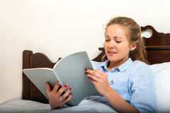 Pretty Young Woman Reading on Bed Royalty Free Stock Images