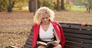 Pretty young woman reading a book on the bench outdoors at sunset. stock footage