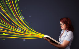 Pretty young woman reading a book while colorful lines are comin Stock Photo