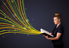 Pretty young woman reading a book while colorful lines are comin Stock Photos