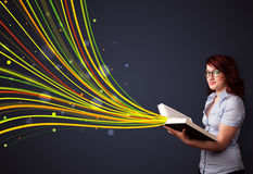 Pretty young woman reading a book while colorful lines are comin Stock Photography