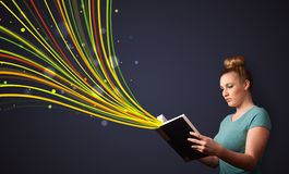 Pretty young woman reading a book while colorful lines are comin Royalty Free Stock Images