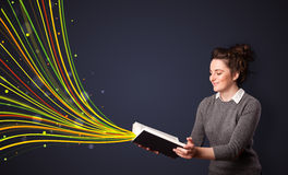 Pretty young woman reading a book while colorful lines are comin Royalty Free Stock Image