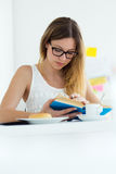 Pretty young woman reading a book and having breakfast at home. Stock Photography