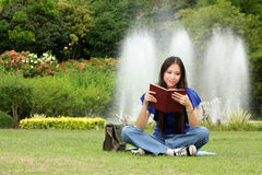 Pretty young woman reading a book at park. With smile Royalty Free Stock Photography
