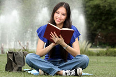 Pretty young woman reading a book at park Royalty Free Stock Image