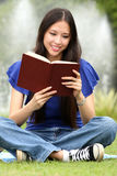 Pretty young woman reading a book at park Stock Images