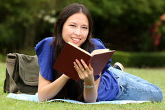 Pretty young woman reading a book at park. With smile Stock Image