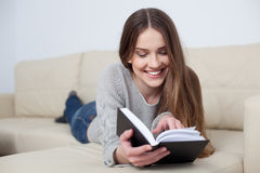 Pretty young woman reading book on sofa Royalty Free Stock Photography