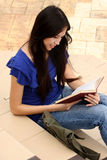 Pretty young woman reading a book at staircase. With smile Royalty Free Stock Photos