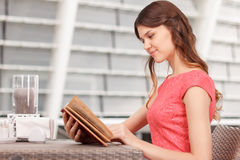 Pretty young woman reading in cafe Royalty Free Stock Images