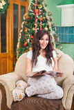 Pretty young woman reading magazine sitting on sofa smiling Stock Photography