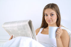 A pretty young woman reading the newspaper in bed and enjoying a cup of tea Royalty Free Stock Photography