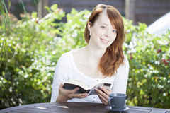 Pretty young woman reading outdoors Royalty Free Stock Photography