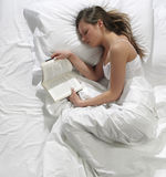 Pretty young woman reads a book Stock Photography