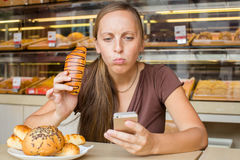 Pretty young woman reads the news on the phone and eating bread. Stock Photography