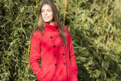 Pretty young woman in red coat Stock Images