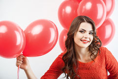 Pretty young woman in red dress is giving present Stock Photos
