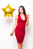 Pretty young woman in red dress with gold star shaped balloon smiling and drinking champagne Stock Photos