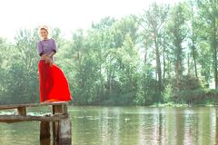 Pretty young woman in red dress posing on the pier Royalty Free Stock Photography