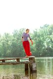 Pretty young woman in red dress posing on the pier Royalty Free Stock Image