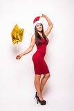 Pretty young woman in red dress and santa christmas hat with gold star shaped balloon Royalty Free Stock Images