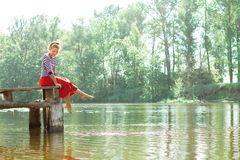Pretty young woman in red dress sitting on pier Stock Photos