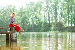 Pretty young woman in red dress sitting on pier Stock Images
