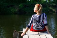 Pretty young woman in red dress sitting on pier Stock Image