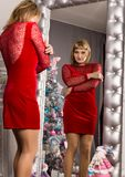 Pretty young woman in red dress stending near wall mirror. Christmas concept royalty free stock photo