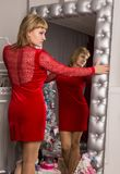 Pretty young woman in red dress stending near wall mirror. Christmas concept royalty free stock photography