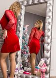Pretty young woman in red dress stending near wall mirror. Christmas concept royalty free stock photos