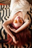 Pretty young woman with red hair and sunglasses lies relaxed and laughing on the couch stock image
