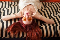 Pretty young woman with red hair and sunglasses lies relaxed and laughing on the couch stock photos