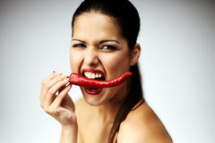 Pretty young woman with a red hot pepper. Royalty Free Stock Photography