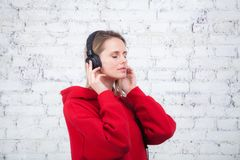 Pretty young woman in red sweatshirt listening to the music with her eyes closed having headphones on and holding it stock photography