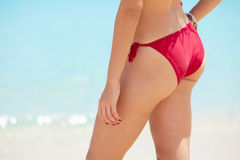 Pretty young woman with red swimsuit near the sea Royalty Free Stock Photography
